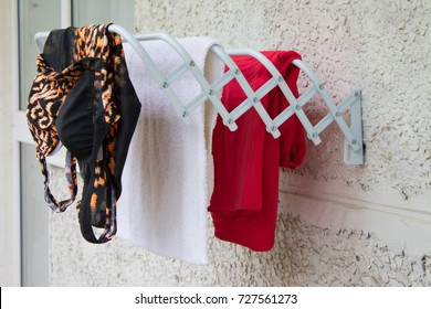 Clothes horse on the balcony. Drying colorful clothes.
