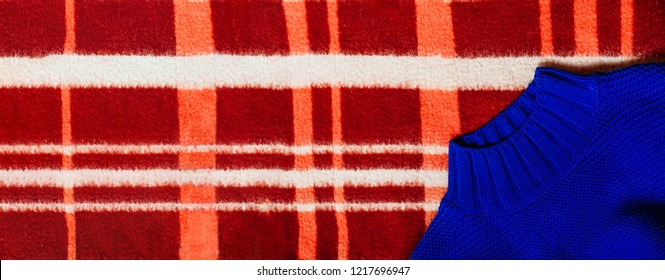 clothes. knitted warm sweater. Blue colour. red striped blanket