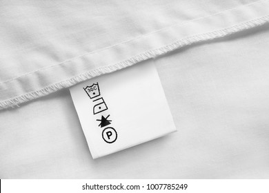 Clothes label with care nstructions on white cotton background