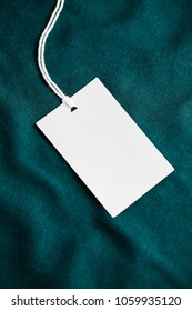 Clothes label tag on dark color cloth background blank white branding template mockup