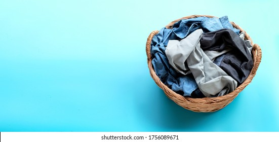 Clothes in laundry basket on blue background. Copy space