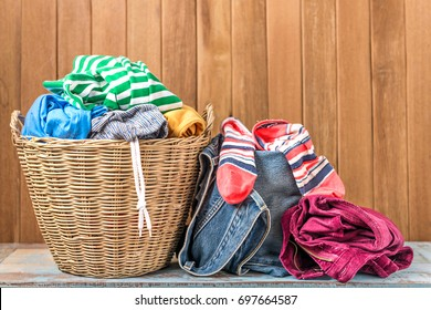 Clothes in a laundry basket on wood table