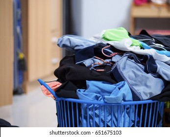 Clothes in laundry plastic basket in the room.