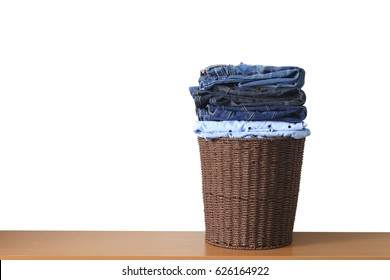 Clothes in a laundry wooden basket on wood table