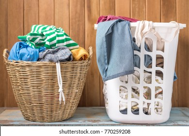 Clothes in a laundry wooden basket and plastic basket on wood table