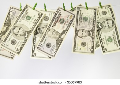 Clothes line of american currency .It is on a white background with green pegs holding the money.