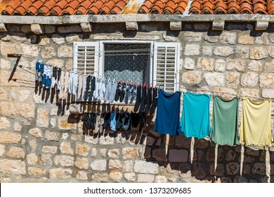 Clothes line with clothes on a house wall