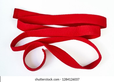 Clothes for martial arts - karate, aikido, judo. Red belt on a white background.