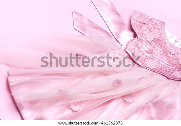Clothes for newborn baby girl on pink background. Copy space for text