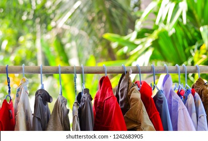 Clothes on hanger hanging to dry on clothesline with blurred green tree background