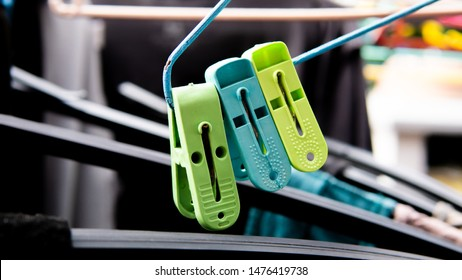 Clothes peg clip on the cloth hanger with laundries drying at background.