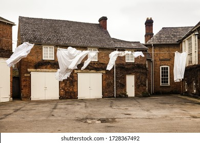 Clothes pegged out on a washing line in the court yard on a grey blustery day