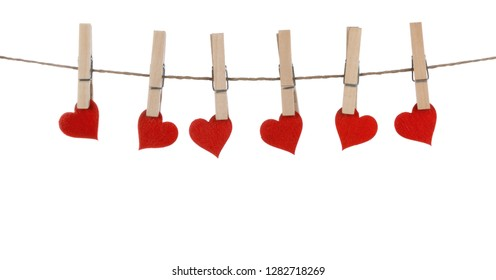 Clothes pegs and red paper hearts on rope isolated on white background Valentines day concept