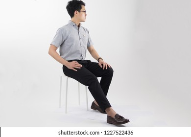 clothes, people, luxury, background, fashion, style concept -   Young asian men sitting on white chair with Gray oxford shirt short sleeve and black slack pants on white background