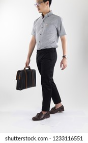 clothes, people, luxury, background, fashion, style concept -   Young asian men carry leather black businees bag with Gray oxford shirt short sleeve and black slack pants on white background