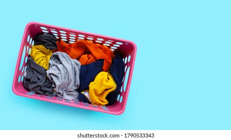 Clothes in pink plastic laundry basket on blue background. Laundry concept