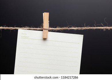 Clothes pins clip on blank memo paper hang on rope and black background. Concept Time control and object images.