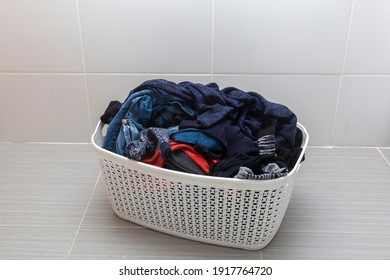 Clothes in plastic laundry basket on isolated  background