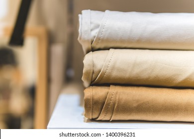 clothes ,sale, shopping, fashion, style concept - Stack of chino pants ,Cream , Brown and khaki color, in the shopping mall
