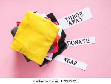 Clothes sorting in home wardrobe for donation, wearing and discard with paper notes on soft pink background.