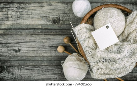 Clothes square label on white balls of wool threads with knitting needles into basket on vintage wooden background. Mock up background for your craft knitting logo or label