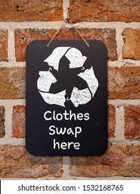 Clothes Swap here text and symbol on chalk board, sustainable fashion and zero waste, recycle clothes and textiles to reduce waste