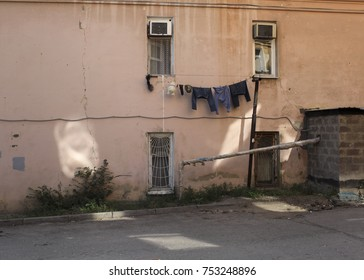 Clothes and a teddy bear on a white rope under the windows of a very old house, Saratov, Russia