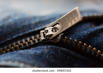 clothes, wear and fashion concept - close up of denim item or jeans zipper