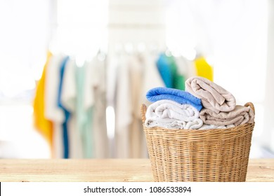 Clothes in wicker basket on wooden table at laundry-Household chore concept.