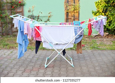 Clotheshorse on cortis. Drying rack with loundry on the garth. Rack dryer with clothes on backyard, sunny day. Clothes rack on the courtyard. Drying horse with airing loundry. Clothes maiden outdoors.