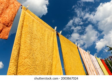 Clothesline with colored clothes and pegs in front of a cloudy sky on a summer day