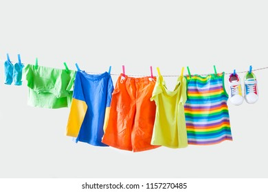 Clothesline with hanging baby clothes on yellow background