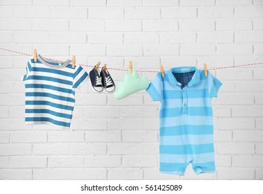 Clothesline with hanging baby clothes on light brick-wall background