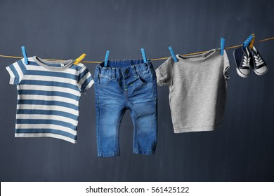 Clothesline with hanging baby clothes on black background