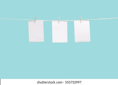 Clothespin hanging with blank photo papers on color background