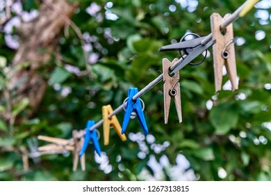 Clothespin hanging on a rope. Plastic and wooden clothespins in different colors