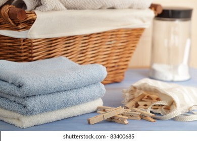 Clothespins in the bag, towels, laundry detergent and a basket in laundry room