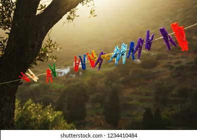 Clothespins on a rope hanging outside house, olive tree and beautiful sunset light