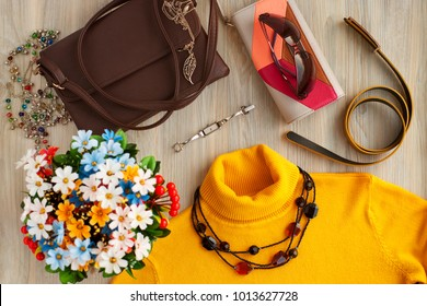 Clothing and accessories for women. Yellow turtleneck, wristwatch, leather purse, handbag, sunglasses for creating a style. Fashion and design of women's clothing and accessories. View from above.