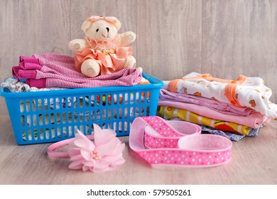 Clothing for children folded into stacks. Sliders and loose jackets stacked in a a stack of. Clothes for babies knitwear. Teddy bear in a pink dress creates a cheerful mood. Clothes for children soft.