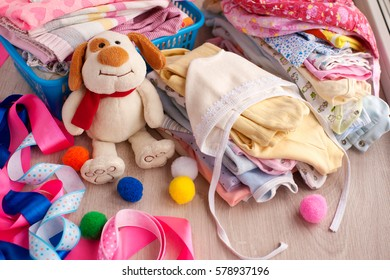 Clothing for children on a wooden surface. Baby clothes folded into stacks. Knitted romper and loose jackets surrounded by ribbons. Toy dog creates a sweet mood. Clothes for children from soft tissue.