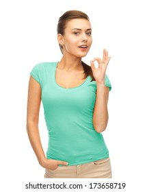 clothing design and happy people concept - smiling girl in blank blue t-shirt showing ok gesture