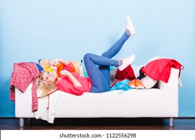 Clothing dilemmas concept. Woman does not know what to wear lying on messy couch with piles of clothes.