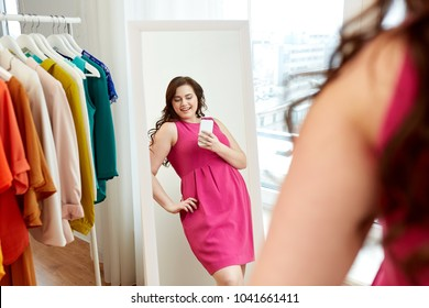 clothing, fashion and people concept - happy plus size woman in pink dress taking at mirror selfie by smartphone at home