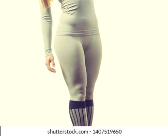 Clothing fashion sport concept. Fit female legs wearing thermoactive underwear pants trousers. Slim woman in sporty clothes