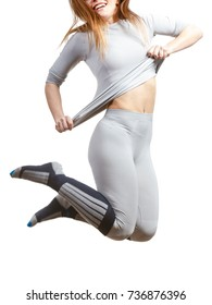 Clothing fashion sport concept. Fit female wearing thermoactive underwear, full body shot. Slim woman in sporty clothes, jumping out of joy.