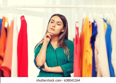 clothing, fashion, style and people concept - woman choosing clothes at home wardrobe