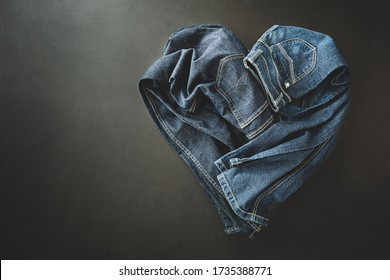 Clothing - heart shape made of two pairs of jeans. Denim trousers captured from above (top view, flat lay). Black chalkboard background with free copy (text) space.
