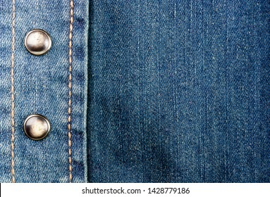 clothing items blue stonewashed faded jeans cotton fabric texture with seams, clasps, buttons and rivets, macro, close-up