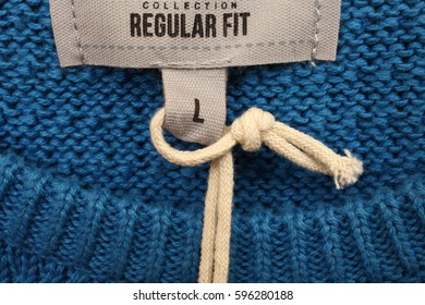 Clothing label on blue wool pullover close up. Background from a natural textile material.